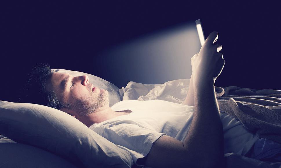 mirar el móvil en la cama